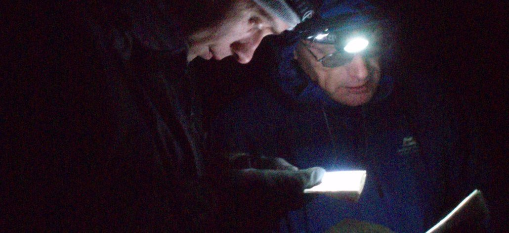 image of two men on Hill Skills Gold Navigation training reading their maps by torch light in night time darkness