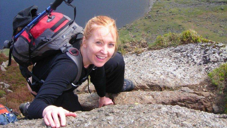 image showing a woman high up Scrambling on Jacks Rake in the Lake District