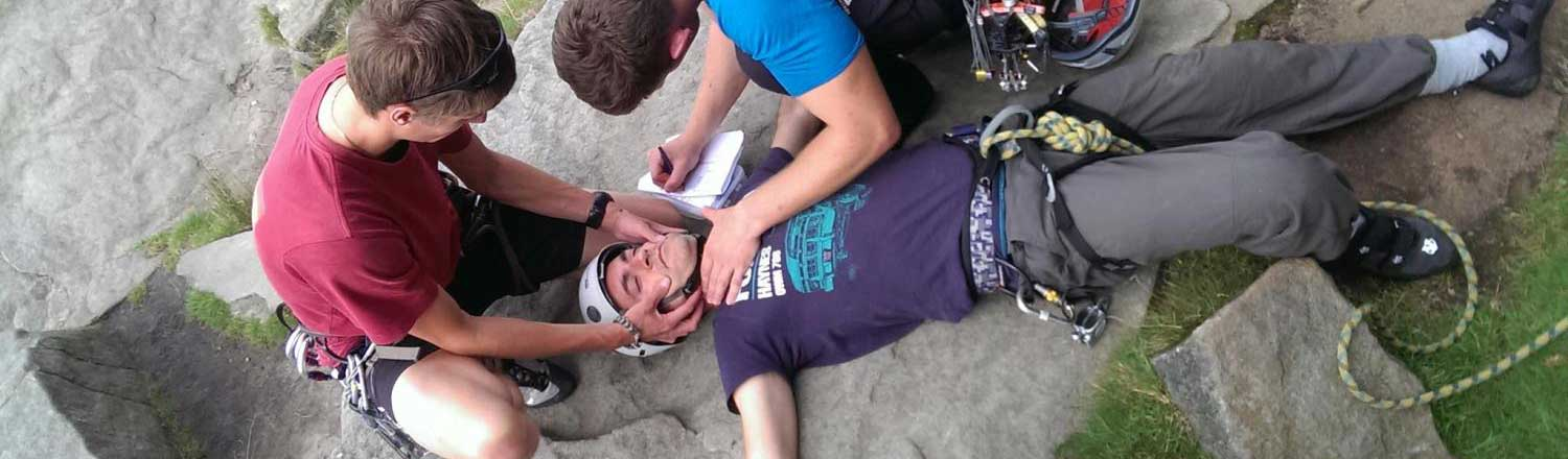 image showing two first-aiders looking after a fallen climber on an Outdoor First Aid course