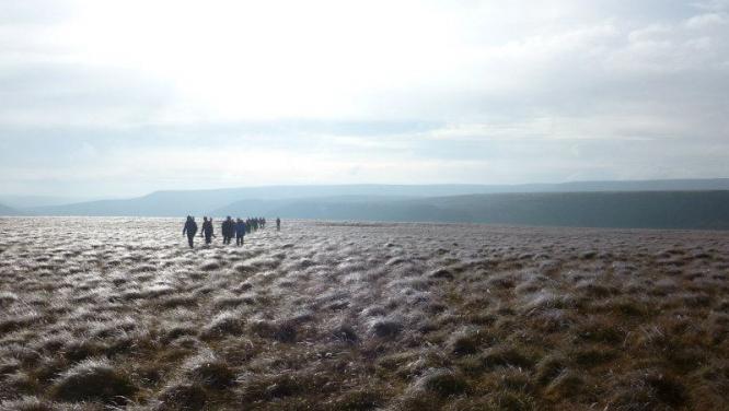 Walkers navigating Howden Moor in the Peak District