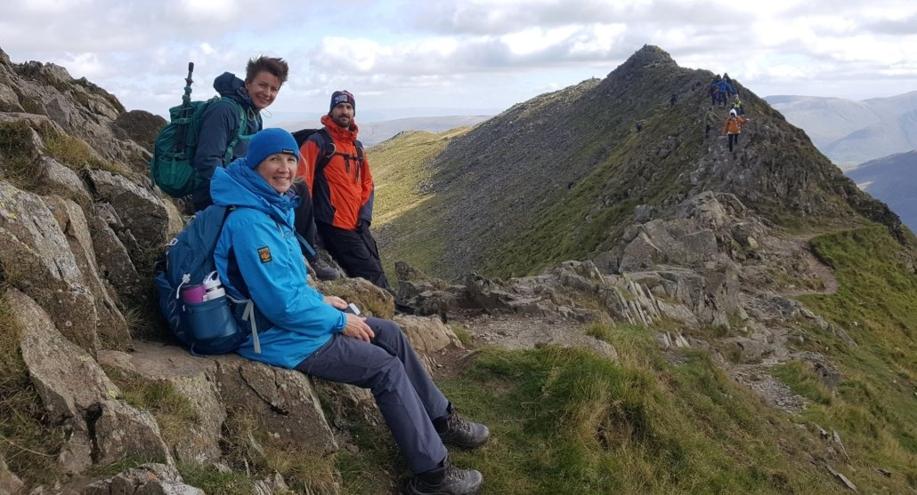 Three walkers sat on Striding Edge in the Lake District