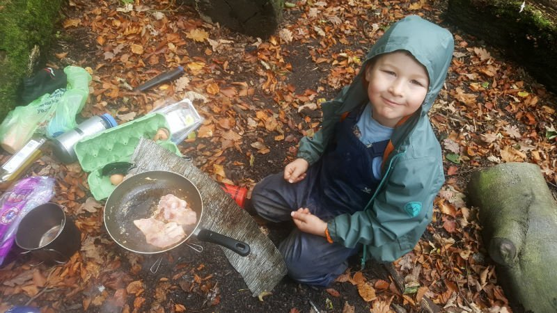Boy cooking lunch on a camping stove