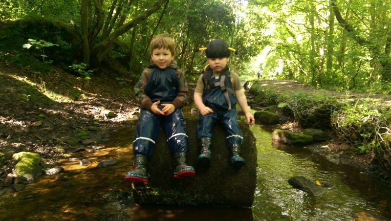 Get your kids walking two boys sat on a boulder in the middle of a stream