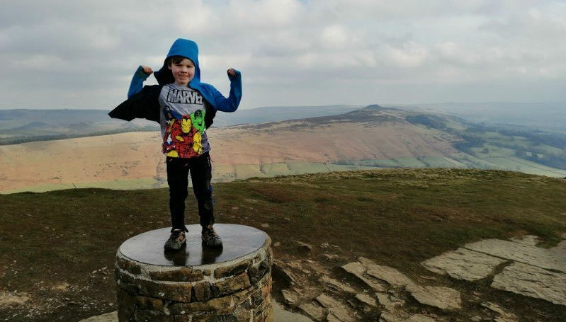 image of a five year old boy standing proudly on top of Lose Hill in the Peak District